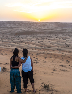 Oman, Al Raka, two young women standing arm in arm on a deseの写真素材 [FYI04334705]