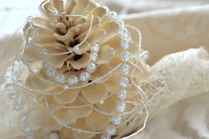 Christmas decoration with fir cone and pearl string, close-uの写真素材 [FYI04334721]