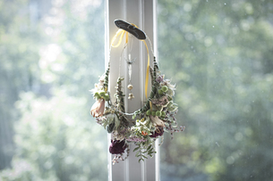 Self-made floral wreath hanging at window catchの写真素材 [FYI04334749]