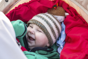 Portrait of laughing baby boy wearing woolly hatの写真素材 [FYI04334780]