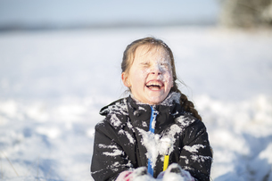 Portrait of laughing girl with snow-covered faceの写真素材 [FYI04334782]