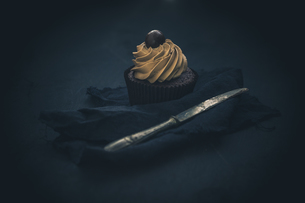 Cupcake with chocolate cream in front of dark backgroundの写真素材 [FYI04334790]