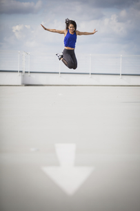 Sporty woman doing jump in the airの写真素材 [FYI04334795]
