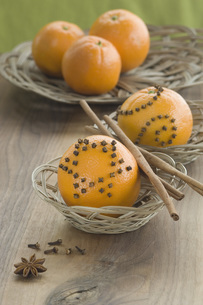 Orange studded with cloves and cinnamon stick in basket besiの写真素材 [FYI04334810]