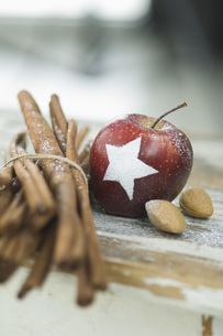 Christmas apple with snow star, cinnamon sticks and almondsの写真素材 [FYI04334816]
