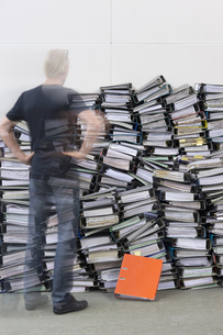 Man standing in front of pile of office filesの写真素材 [FYI04334834]