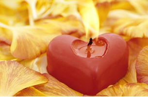 Candle in shape of a heart burning, with flower leavesの写真素材 [FYI04334857]