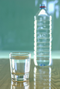 Glass of water by plastic bottle, close-upの写真素材 [FYI04334978]