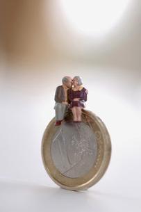 Senior couple sitting on coinの写真素材 [FYI04334983]