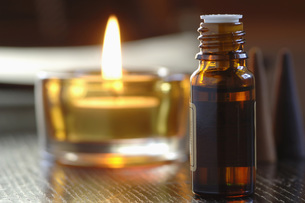 Bottle of scented oil, beside a tealight, close-upの写真素材 [FYI04335006]