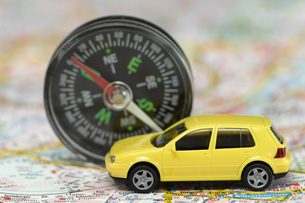 Toy car and compass on city map, close upの写真素材 [FYI04335012]