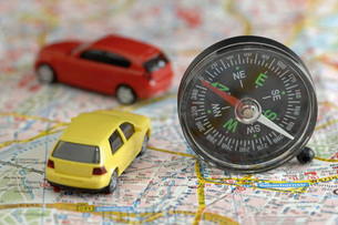 Toy cars and compass on city map, close upの写真素材 [FYI04335013]