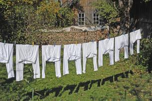 Gemany, Buchendorf, Washing line with pyjamas in backyardの写真素材 [FYI04335023]