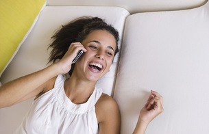 Teenage girl lying on white couch and using cell phone, smilの写真素材 [FYI04335036]