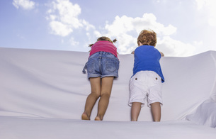 Spain, Boy and girl standing and looking over white couchの写真素材 [FYI04335040]