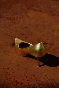 Golden stiletto on a rusty tableの写真素材 [FYI04335092]