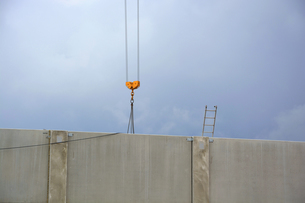 Crane and ladder behind a concrete wallの写真素材 [FYI04335109]