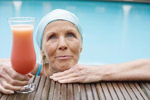 Germany, senior woman having cocktail at poolの写真素材 [FYI04335130]