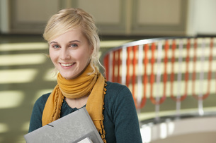 Germany, Leipzig, Young woman standing with books in hallwayの写真素材 [FYI04335140]