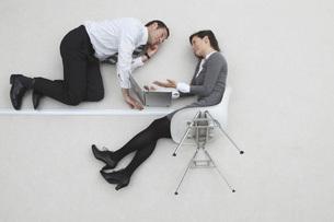 Businessman and businesswoman using laptop, portrait, elevatの写真素材 [FYI04335146]
