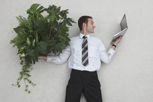 Businessman holding laptop and Foliage Plants, portraitの写真素材 [FYI04335148]