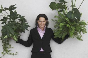 Businesswoman holding Foliage Plants, portrait, elevated vieの写真素材 [FYI04335149]