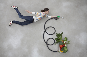 Mid adult woman holding industrial hose connected to vegetabの写真素材 [FYI04335155]