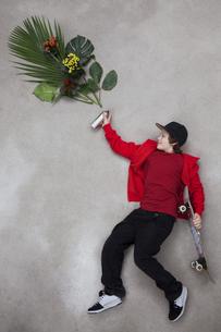 Boy spraying leaves from spray bottleの写真素材 [FYI04335158]