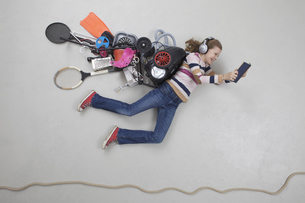 Girl with gadgets reading bookの写真素材 [FYI04335193]