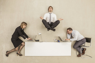 Businessman meditating above office desk while others workinの写真素材 [FYI04335205]