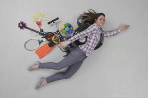 Mid adult woman flying, smiling, portraitの写真素材 [FYI04335211]