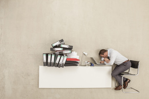 Businessman sleeping on office desk with stack of filesの写真素材 [FYI04335214]
