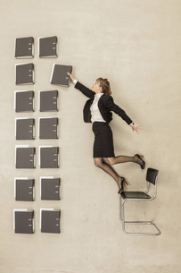 Businesswoman standing on office chair arranging filesの写真素材 [FYI04335216]