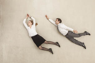 Businessman and businesswoman flying against beige backgrounの写真素材 [FYI04335219]