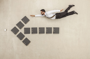 Businessman flying above files forming arrow signの写真素材 [FYI04335221]