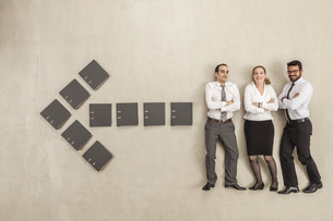 Business people standing along arrow sign formed by filesの写真素材 [FYI04335224]