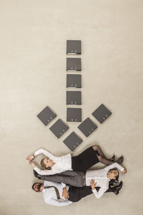 Business people lying below down arrow sign formed by filesの写真素材 [FYI04335225]