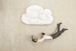 Businessman using laptop and flying below cloud shape pillowの写真素材 [FYI04335229]