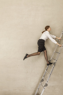 Businesswoman climbing ladder in officeの写真素材 [FYI04335232]