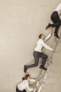 Business people climbing ladder in officeの写真素材 [FYI04335233]