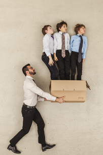 Businessman holding cardboard box while boys flying outの写真素材 [FYI04335244]