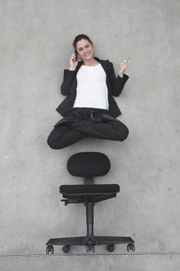 Businesswoman using mobile phone floating above chair, elevaの写真素材 [FYI04335273]