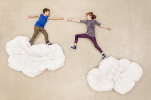 Children jumping over cloudsの写真素材 [FYI04335274]