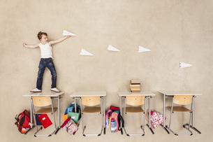 Boy throwing paper planesの写真素材 [FYI04335278]