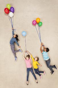 Children flying away on balloonsの写真素材 [FYI04335291]
