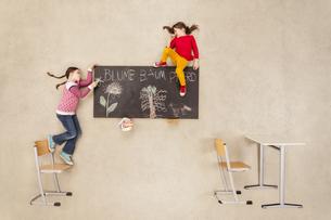 School kids drawing on blackboardの写真素材 [FYI04335300]