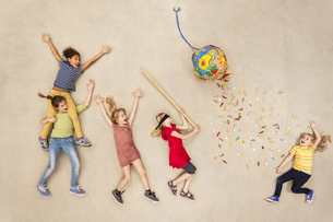 Children hitting ballon with candies at partyの写真素材 [FYI04335309]