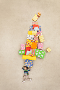 Boy balancing stack of presentsの写真素材 [FYI04335314]
