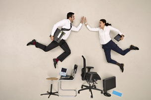 Business colleagues flying over chairs high fivingの写真素材 [FYI04335318]