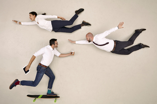 Two business colleagues flying, one colleague skateboardingの写真素材 [FYI04335319]